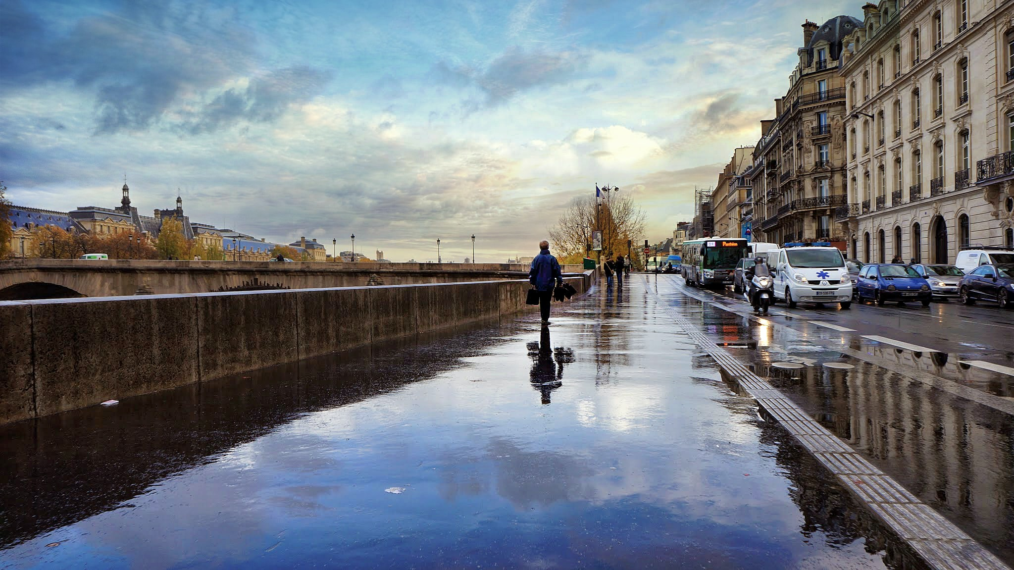 Wet sidewalk and busy daytime traffic on city street with reflection at Musée d'Orsay