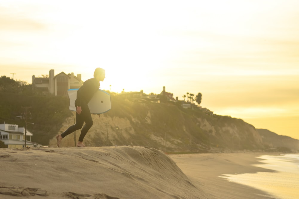 man carrying white bodyboard on gray sand beach
