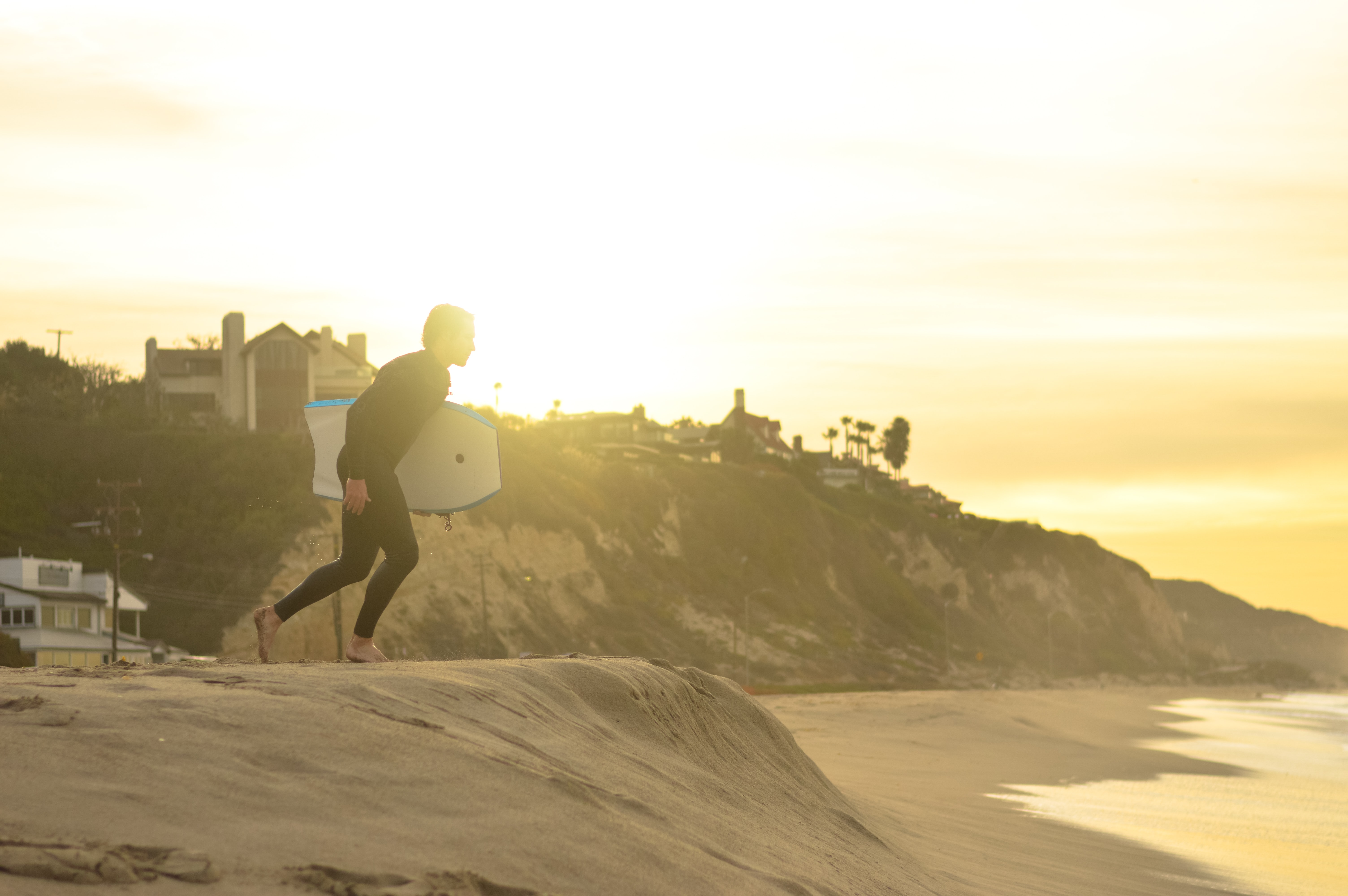 A surfer in a wetsuit, with his surfboard under his arm, running across the sand towards the sea at sunset