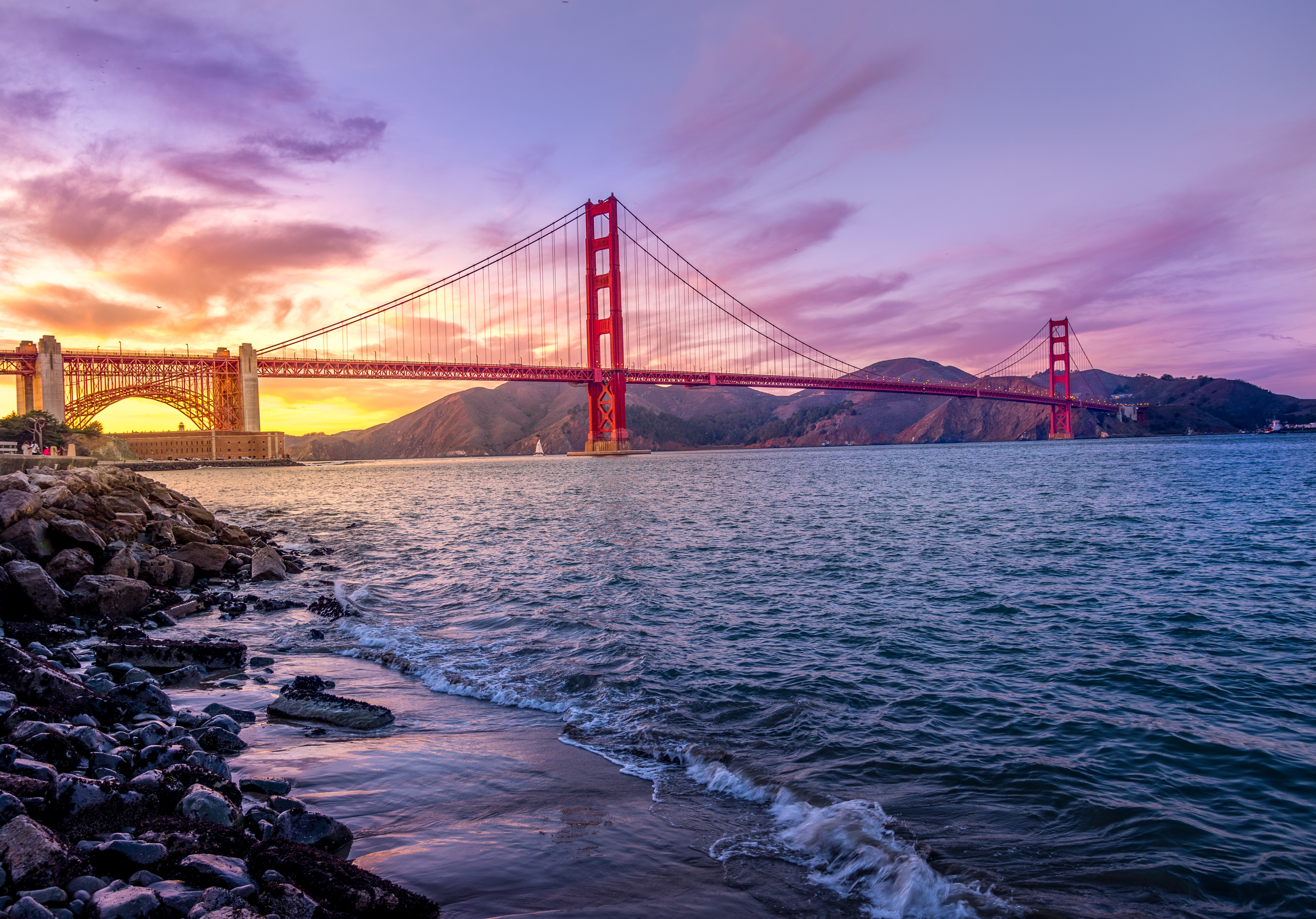 A purple and yellow sunset behind Golden Gate Bridge in San Fransisco, with waves breaking on the shoreline.