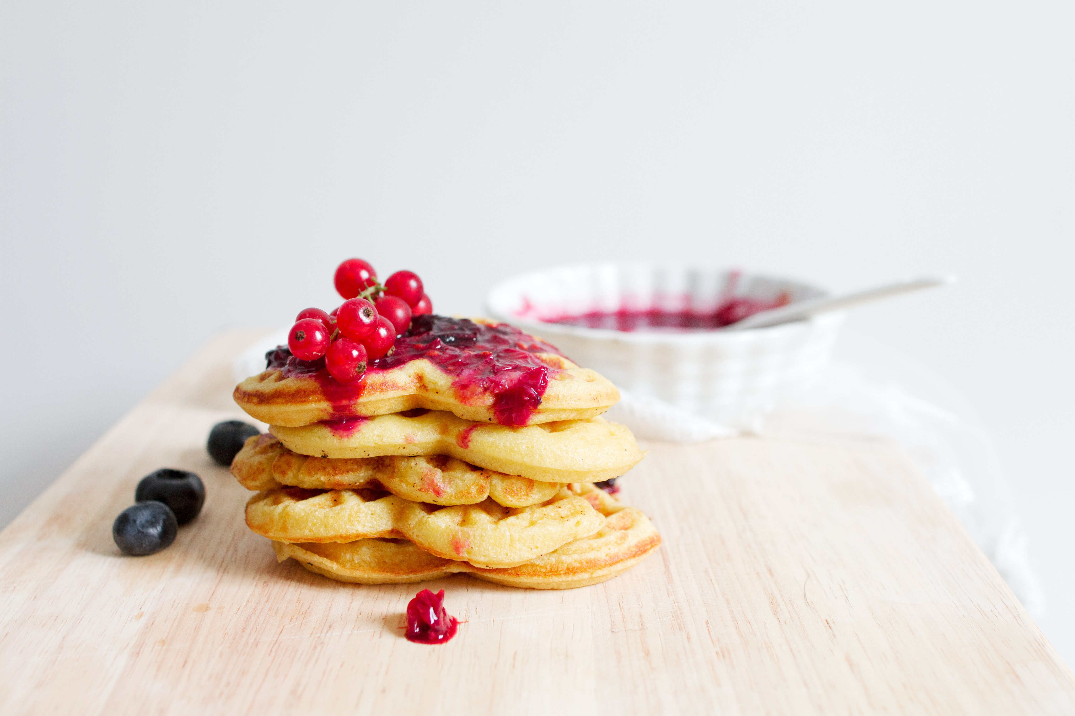 Red currants, blueberries and marmalade on a stack of heart-shaped waffles