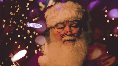 bokeh photography of santa claus santa's elves zoom background