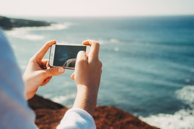 person standing on cliff taking photo of body of water during daytime