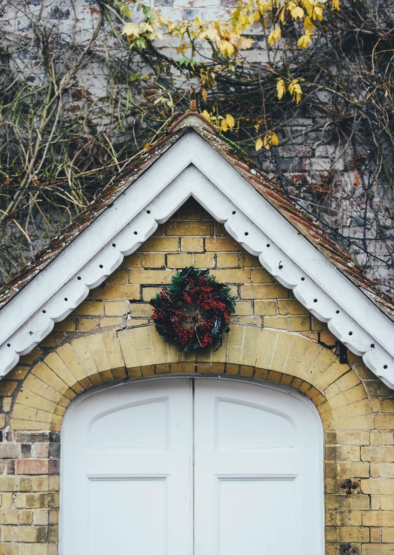 red flower wreath over door