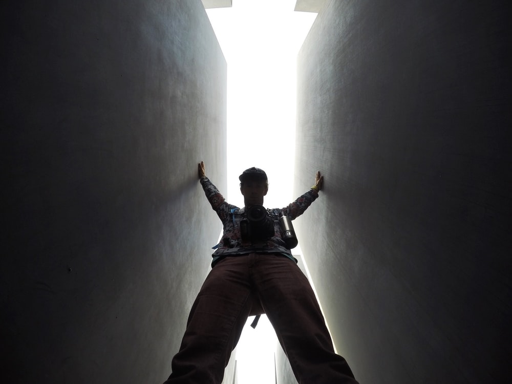 low-angle photo of man standing between walls