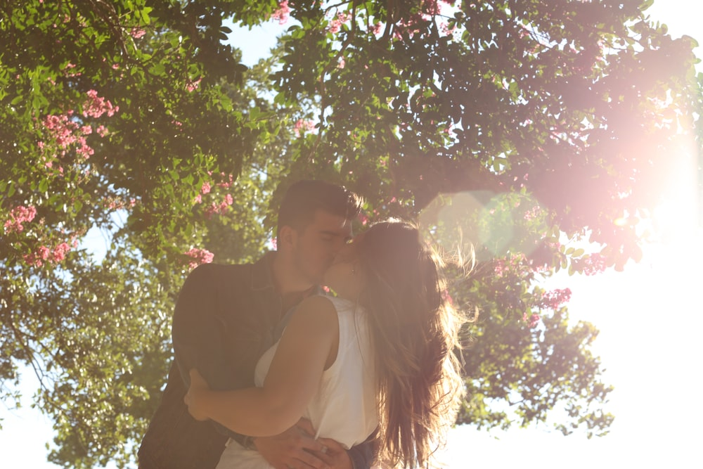 man kissing woman under green tree during daytime