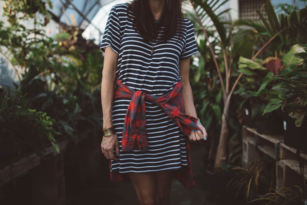 woman wearing black and white striped dress standing in isle near green plants