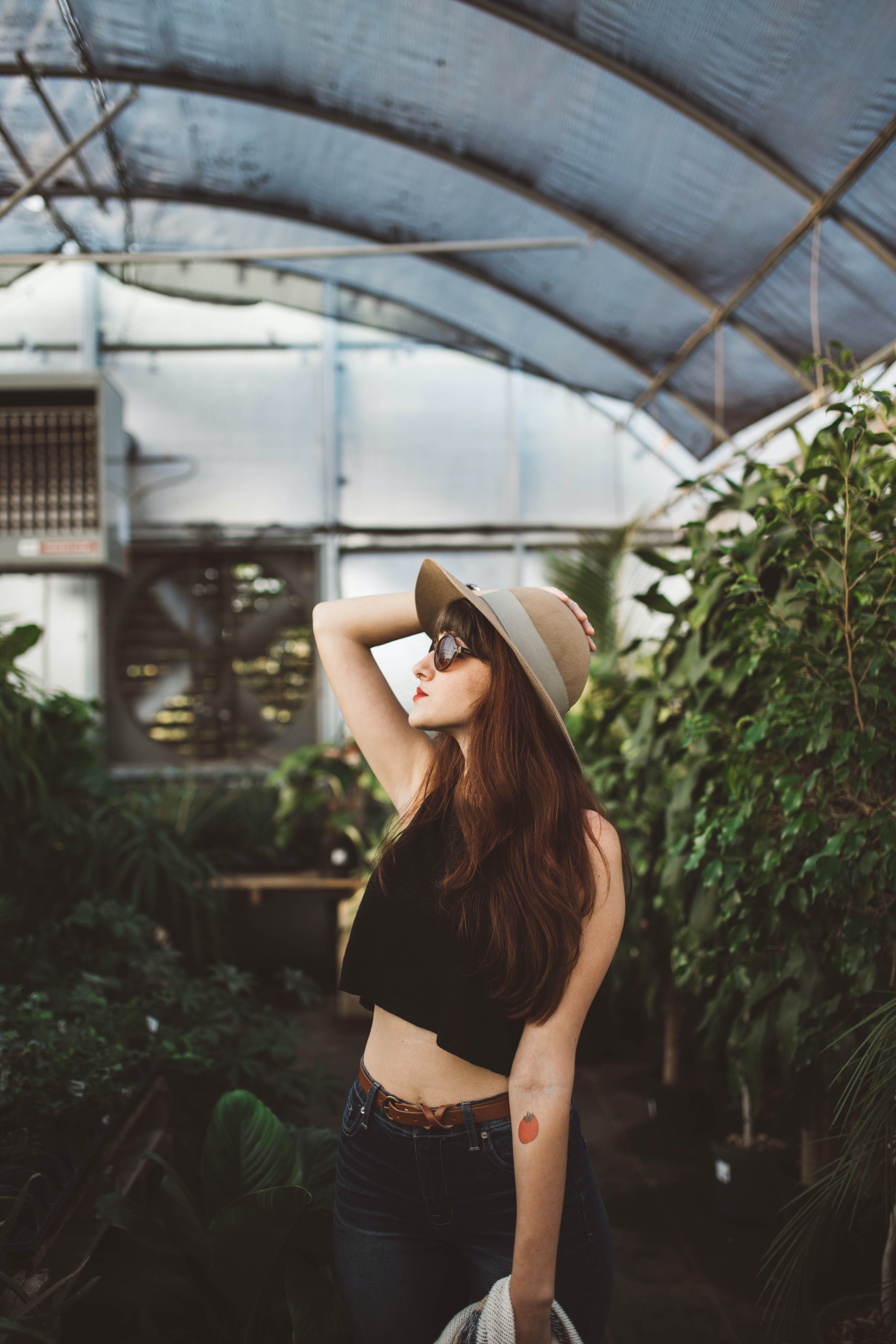 shallow focus photography of woman posing while holding her hat at the garden