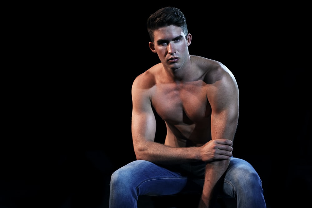 topless man wearing blue denim jeans sitting