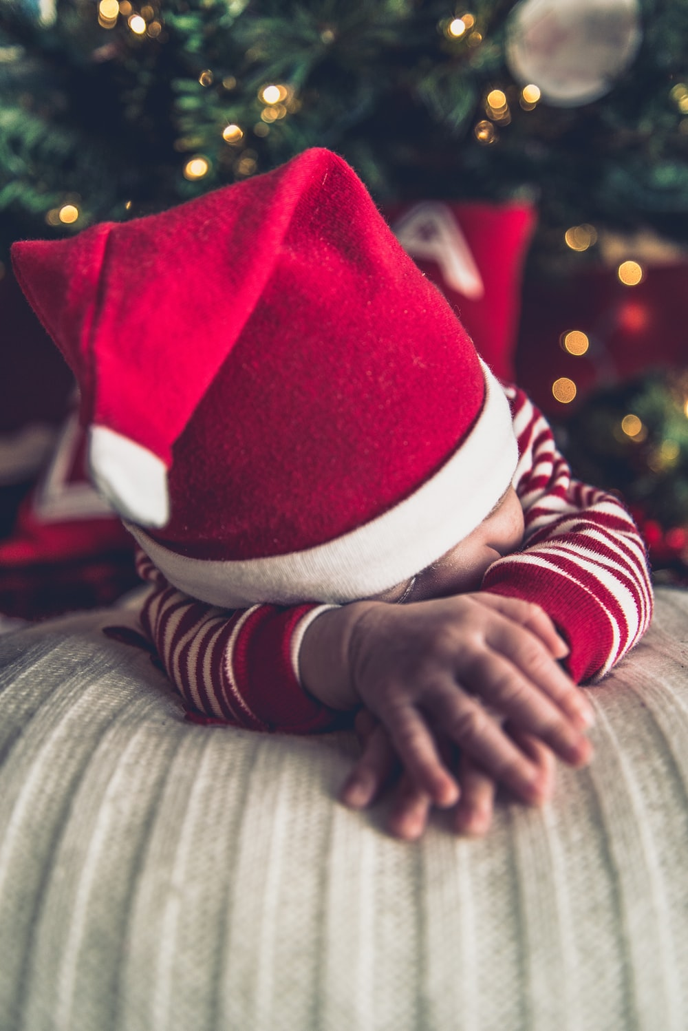 A baby wearing a Christmas outfit and Santa hat.