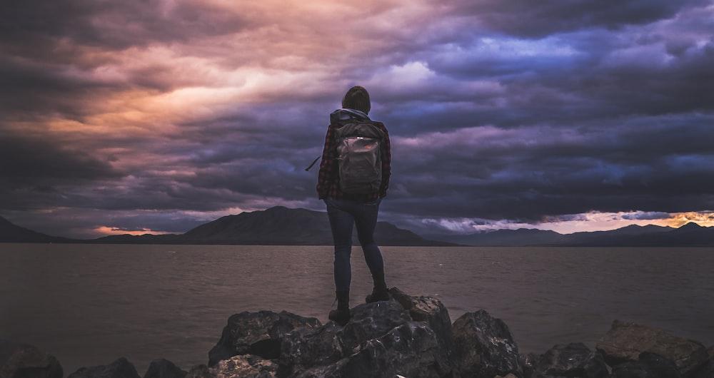 man standing on rock overlooking ocean