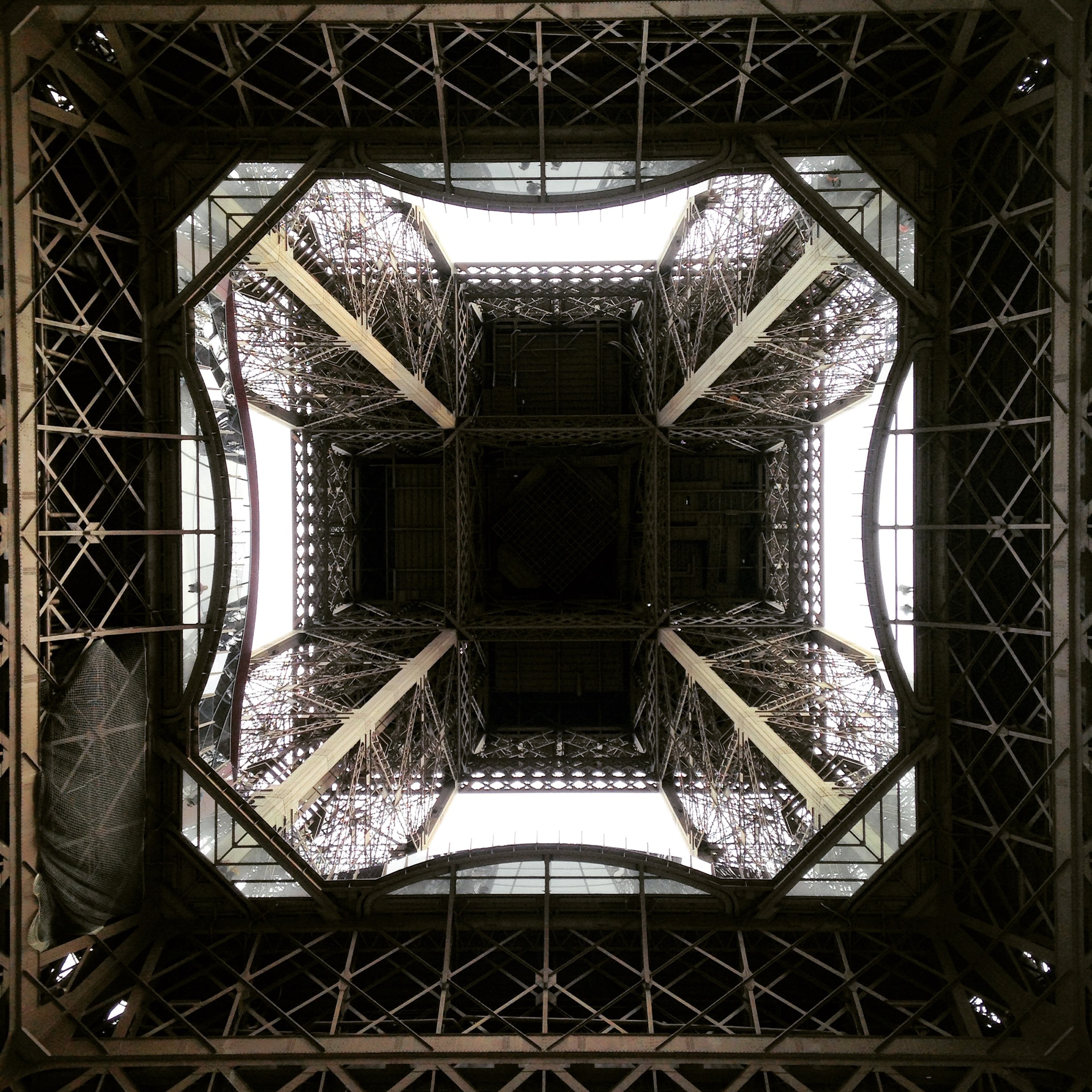 Street view looking inside the architecture of the Eiffel Tower in Paris, France.
