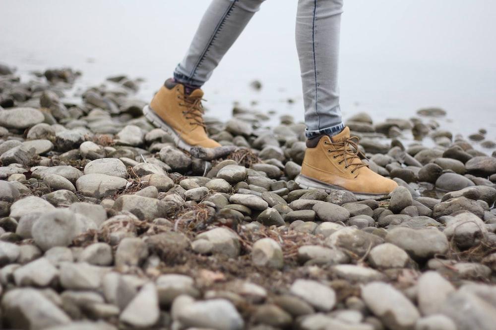 person wearing brown shoes walking through stoned seashore