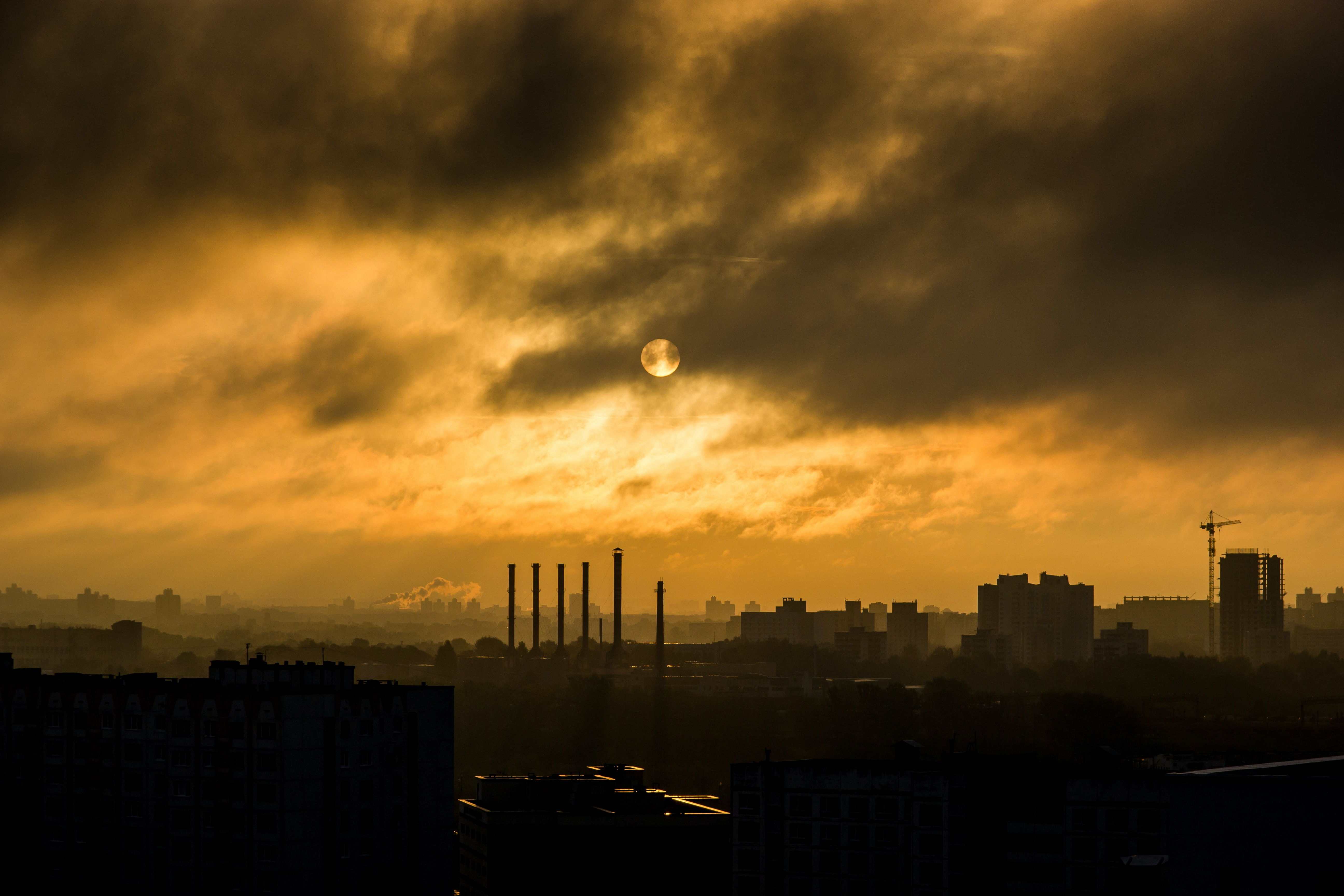 The sun is surrounded by clouds above the city of Минск during sunset.