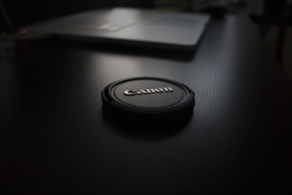 shallow focus photography of black Canon zoom lens cover