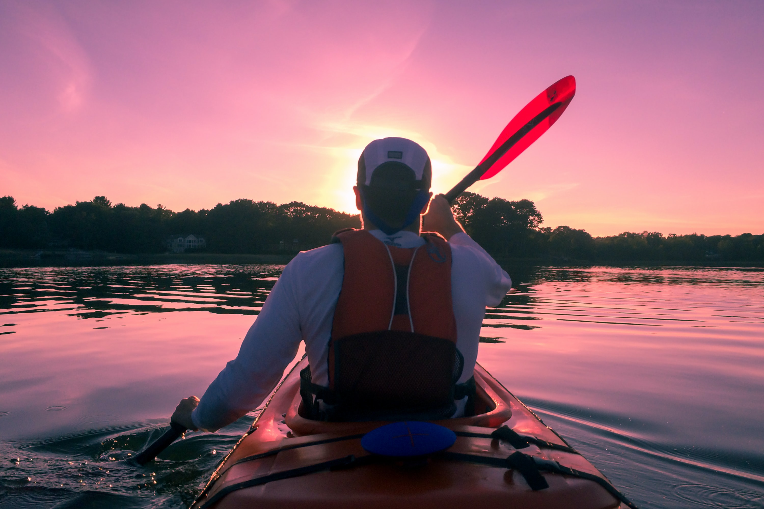 A man in a lifejacket rowing a kayak on a river at sunset