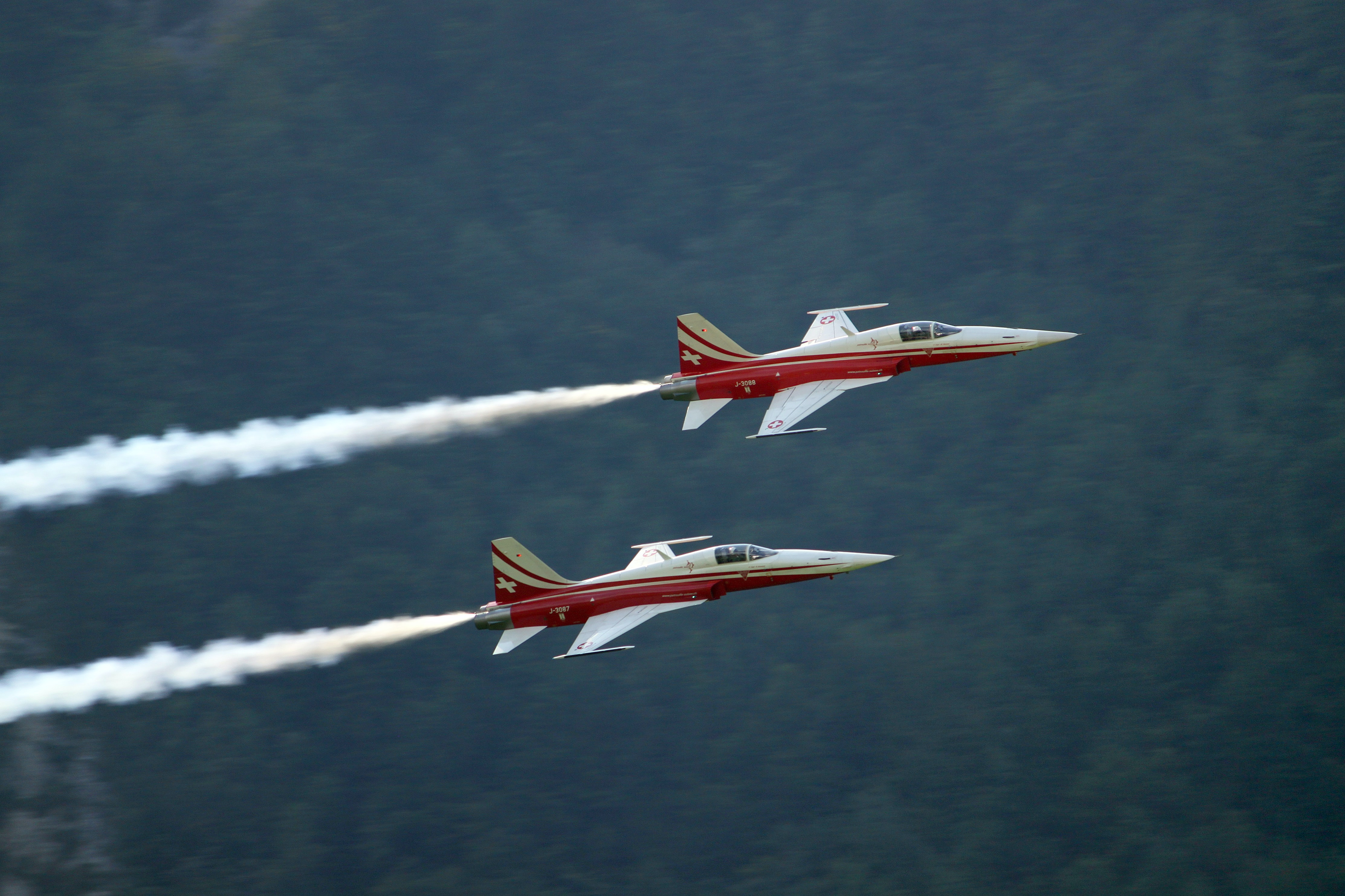 two red-and-white jet planes on air