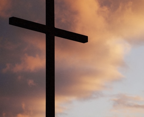 silhouette of large cross under orange sky
