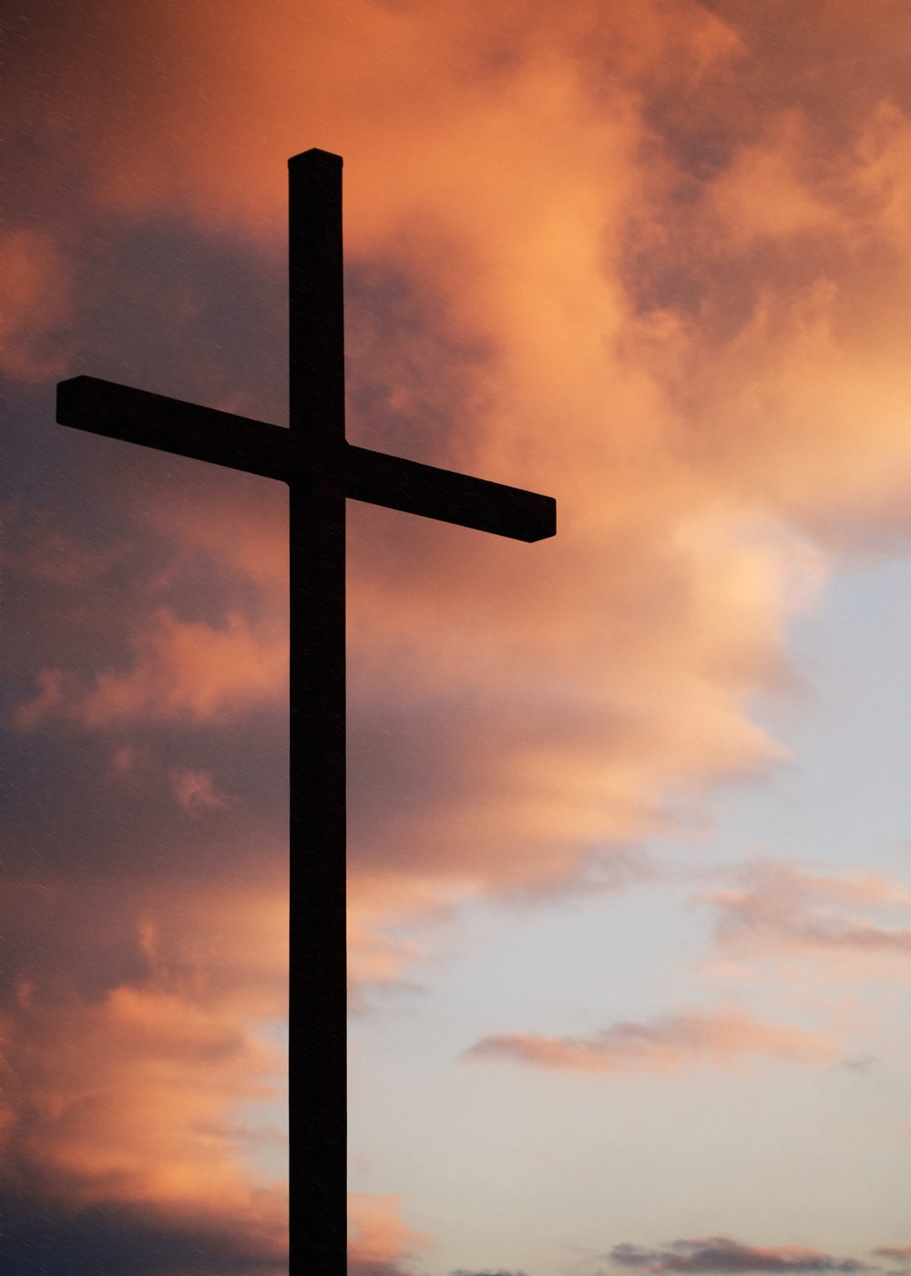 A cross against the colored sunset sky