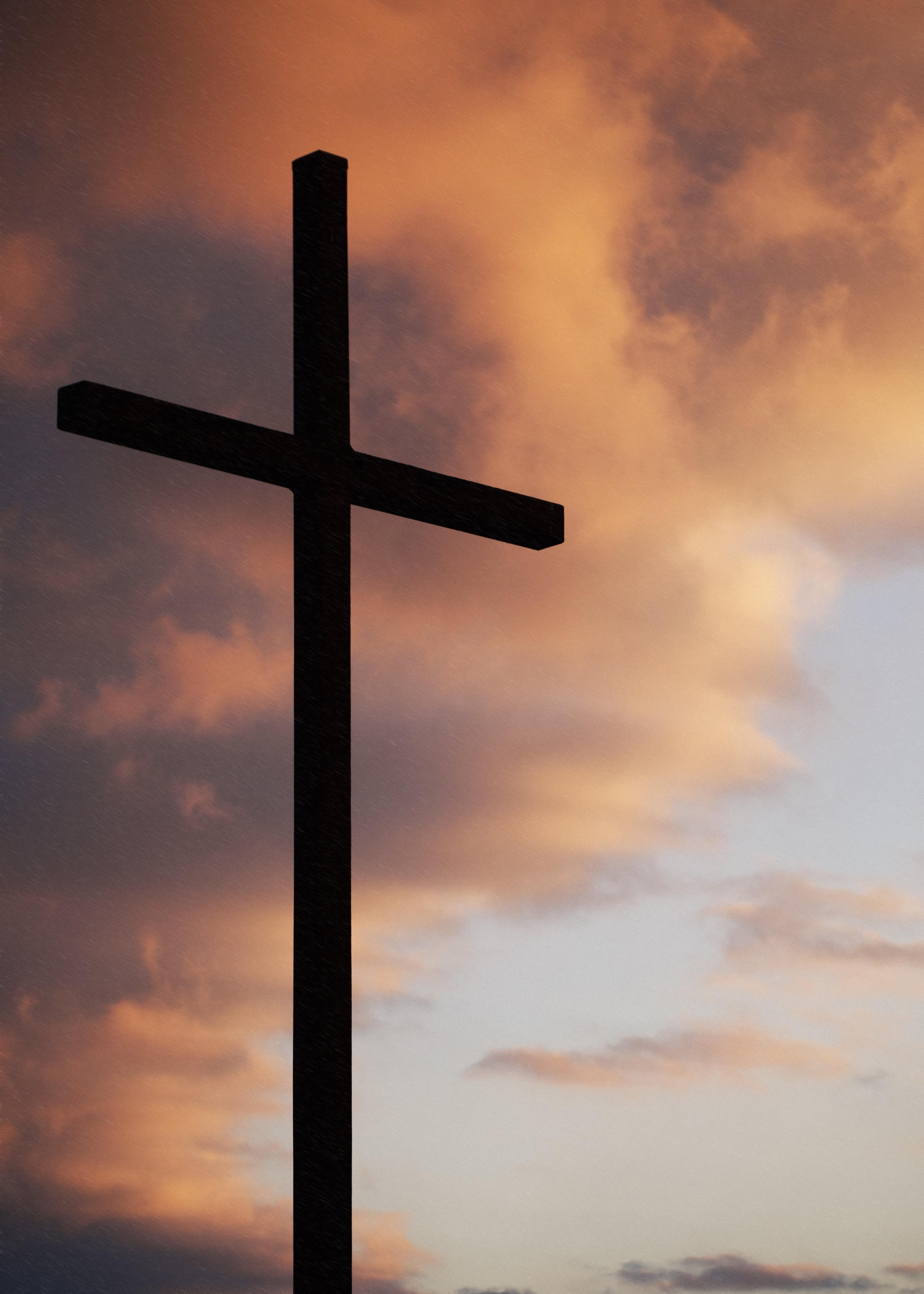 silhouette of large cross under orange sky
