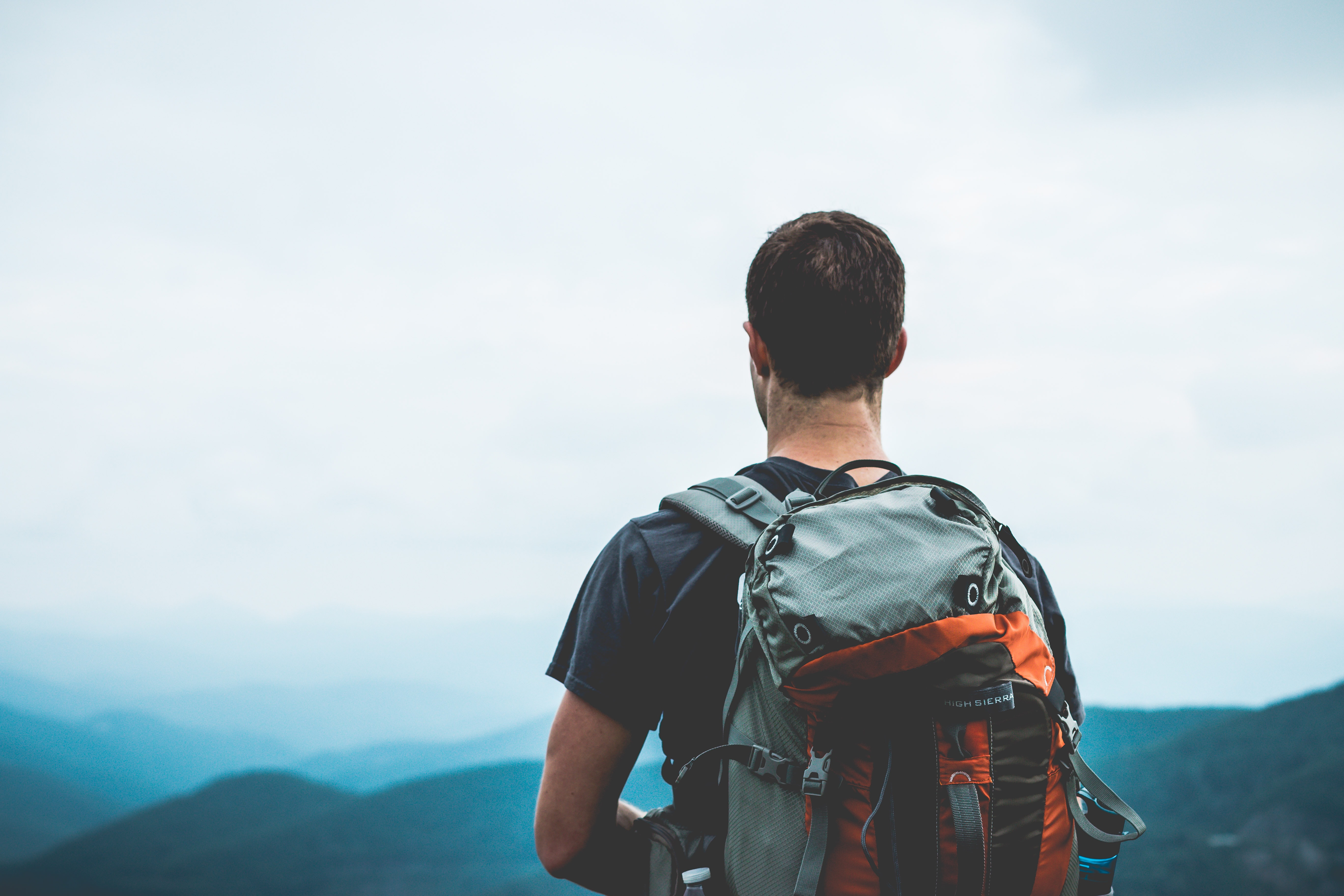 Standing behind a hiker who's made it to the top of a mountain