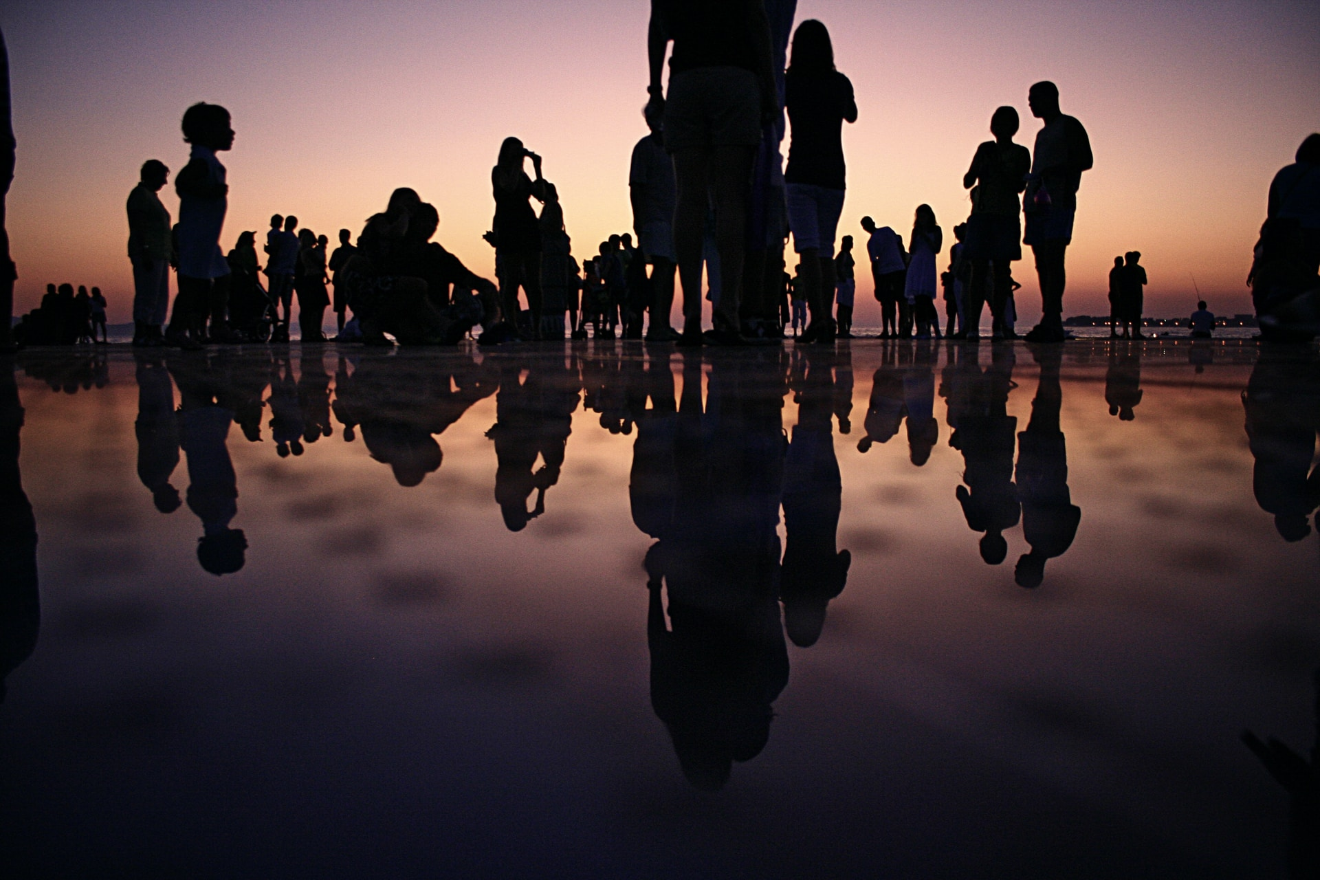 silhouette of people standing on mirror during golden hour