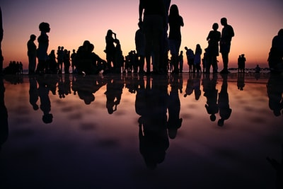 silhouette of people standing on mirror during golden hour people teams background