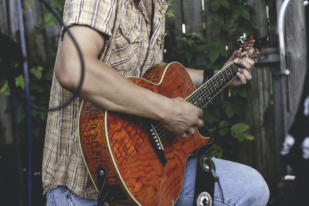 person holding brown guitar outdoor