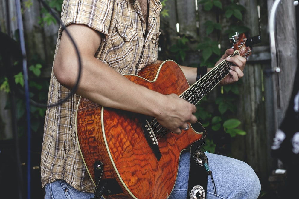 A man in a checkered shirt strumming an acoustic guitar in a garden