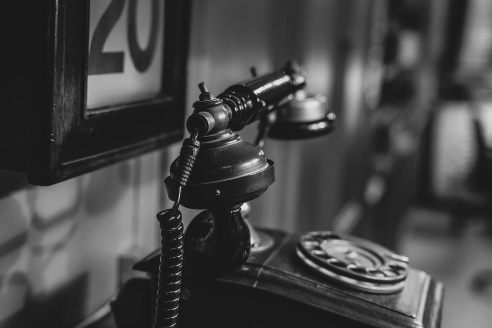 candlestick telephone in monochrome photo