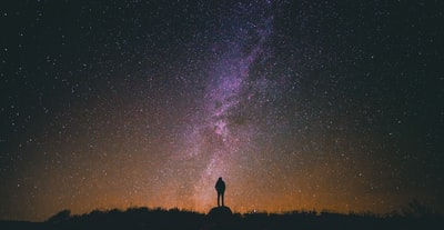 silhouette of man standing on rock while looking in sky universe teams background