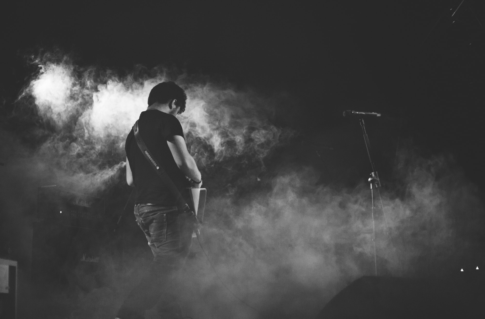 A black-and-white shot of a male musician with a guitar in smoke on stage