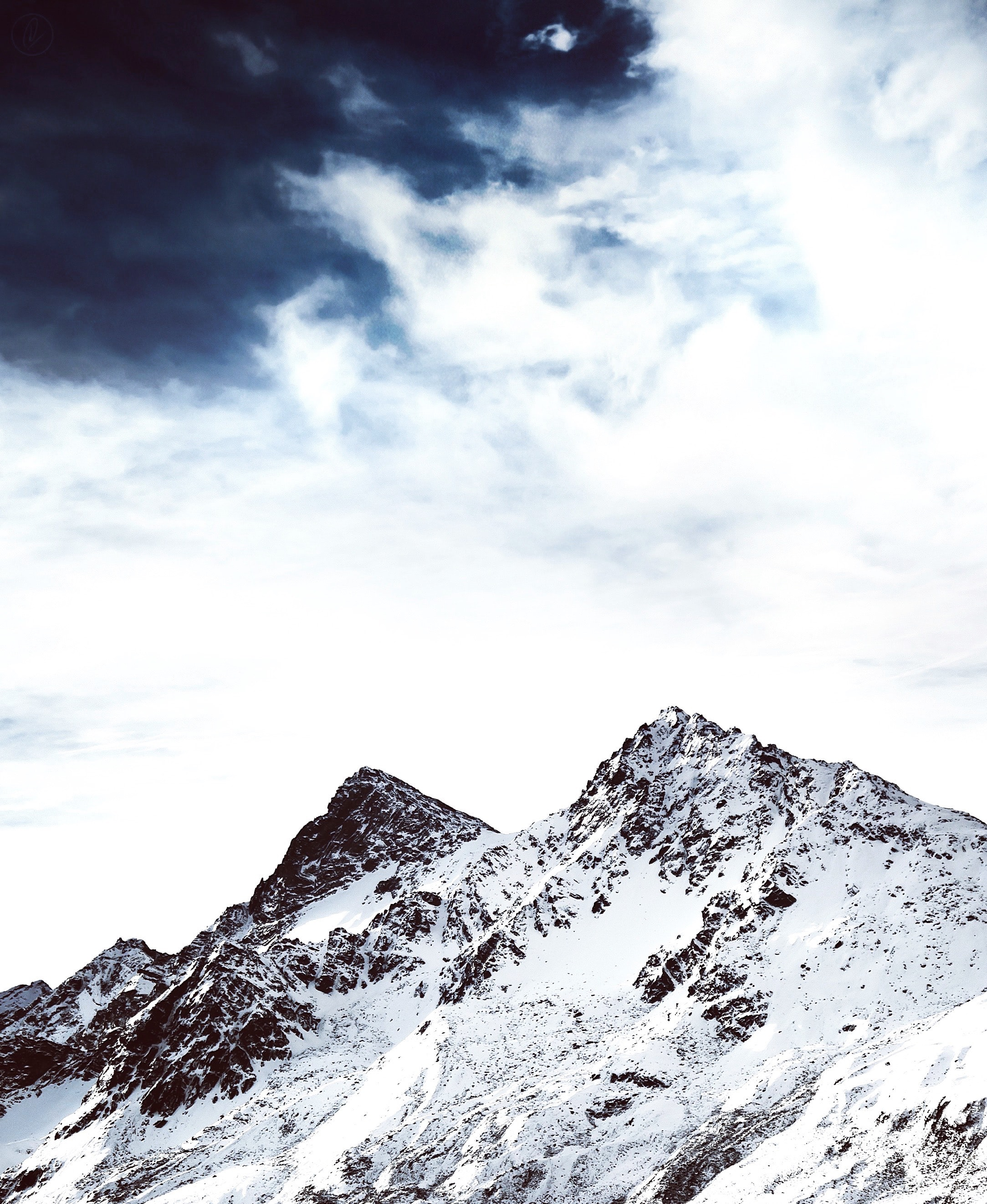 A mountain peak in the snow with a dramatic cloudy sky