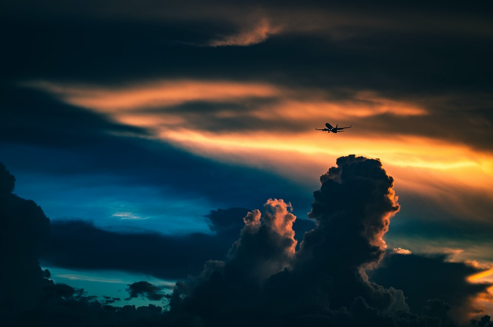 silhouette of plane under cloudy skies