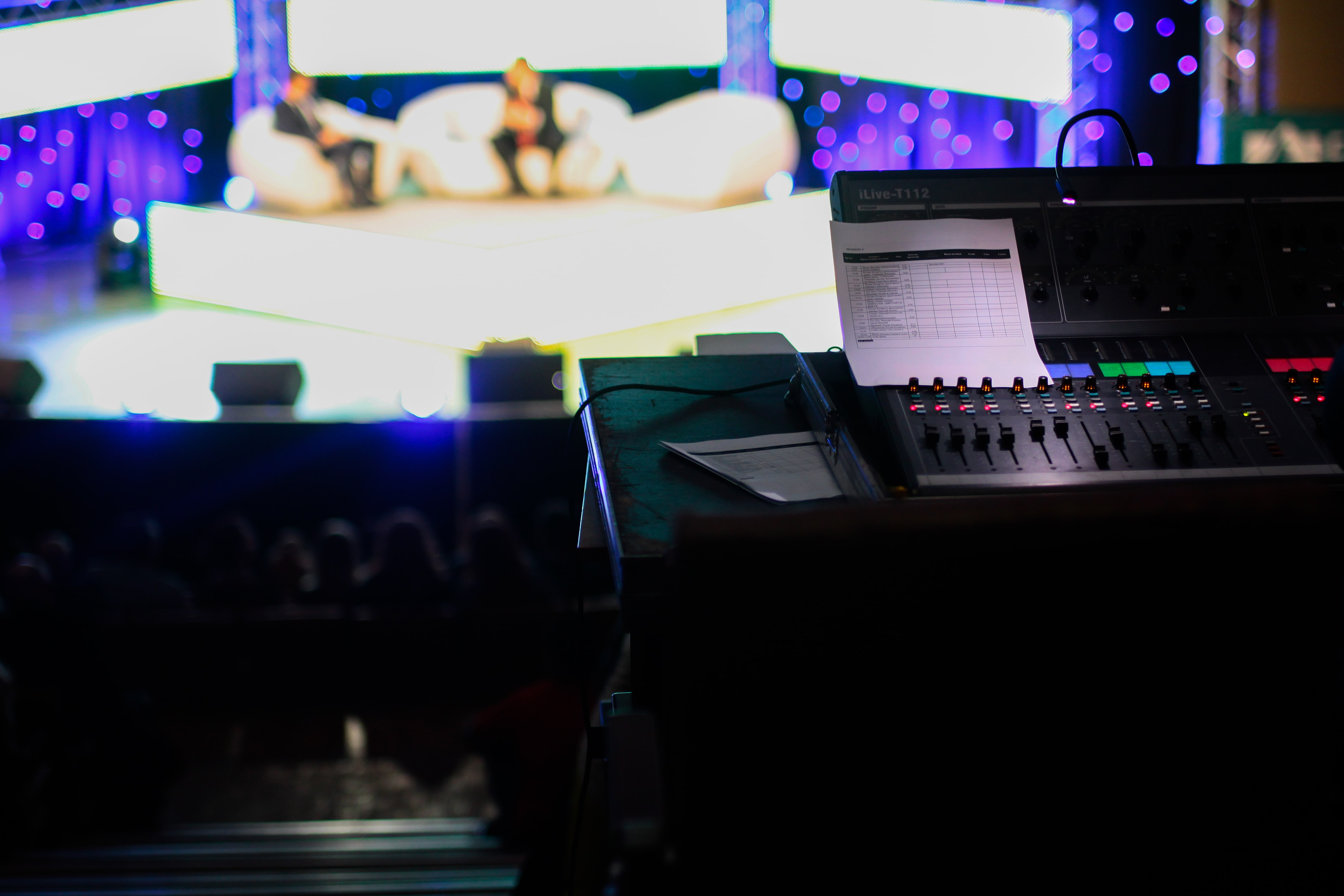 A sound and lighting board at the back of a set with an audience sitting in front of a live production