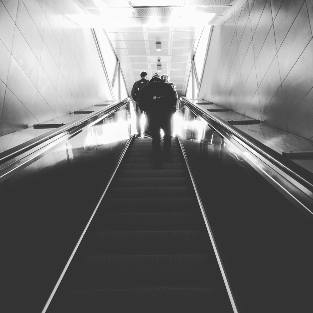 grayscale photography of man on escalator