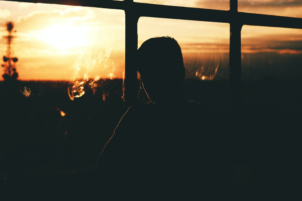 silhouette of a person by a glass window during sunset