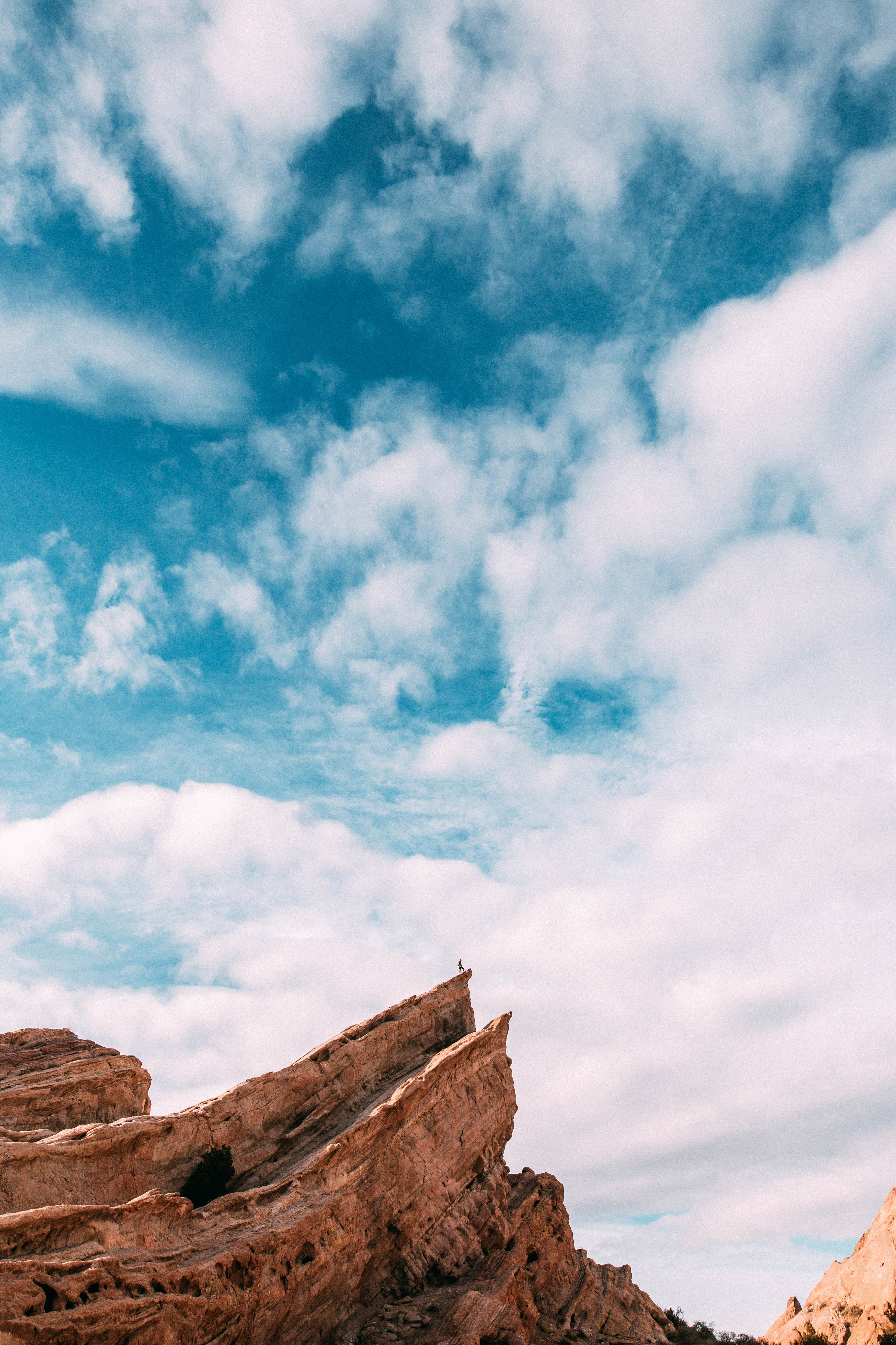 A distant silhouette on a hiker on top of a slanted orange rock ledge under a cloudy azure sky