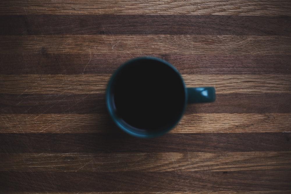 black ceramic mug on wooden surface