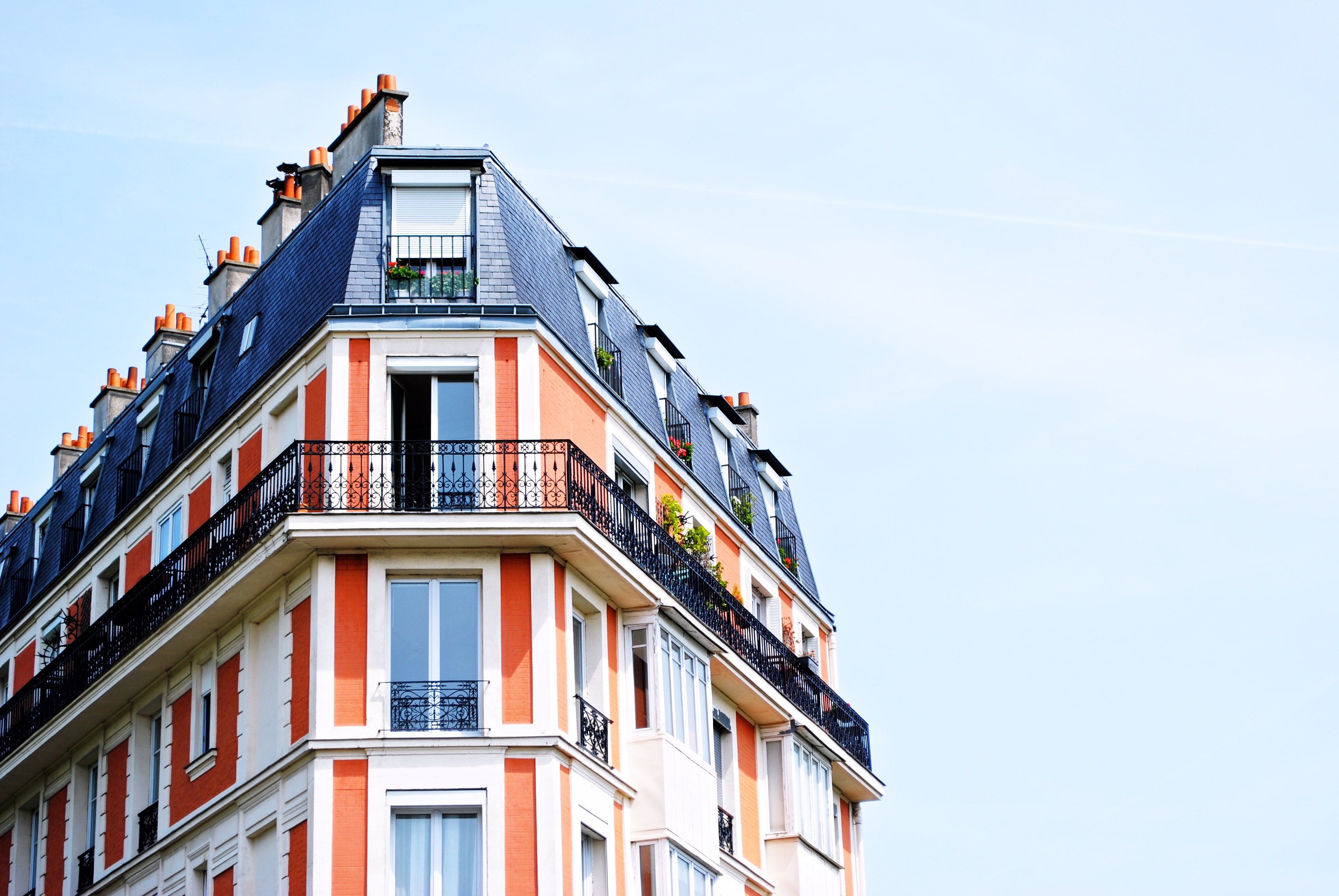 A bright, colorful shot of the corner of a blue and orange building in Paris