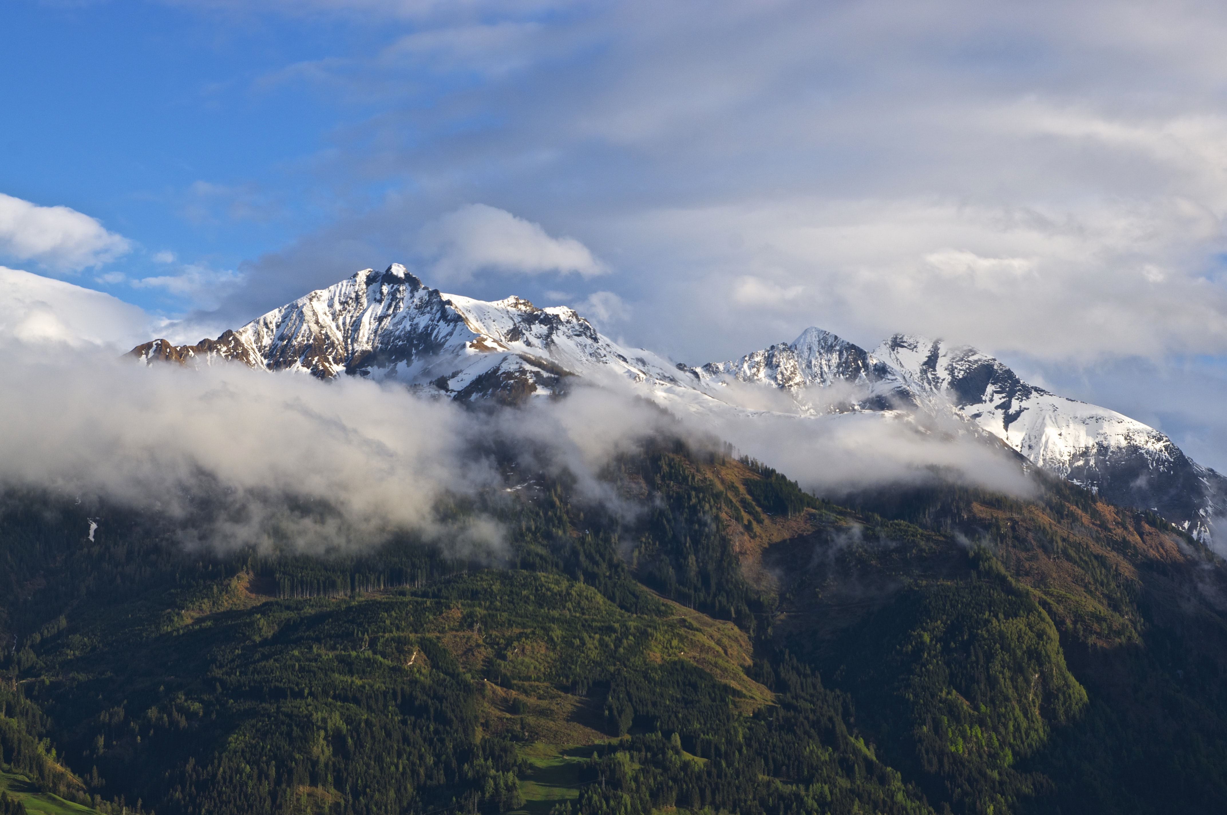 Snow covered mountains with a lush green bottom covered by moving clouds and a blue sky in Fürth.