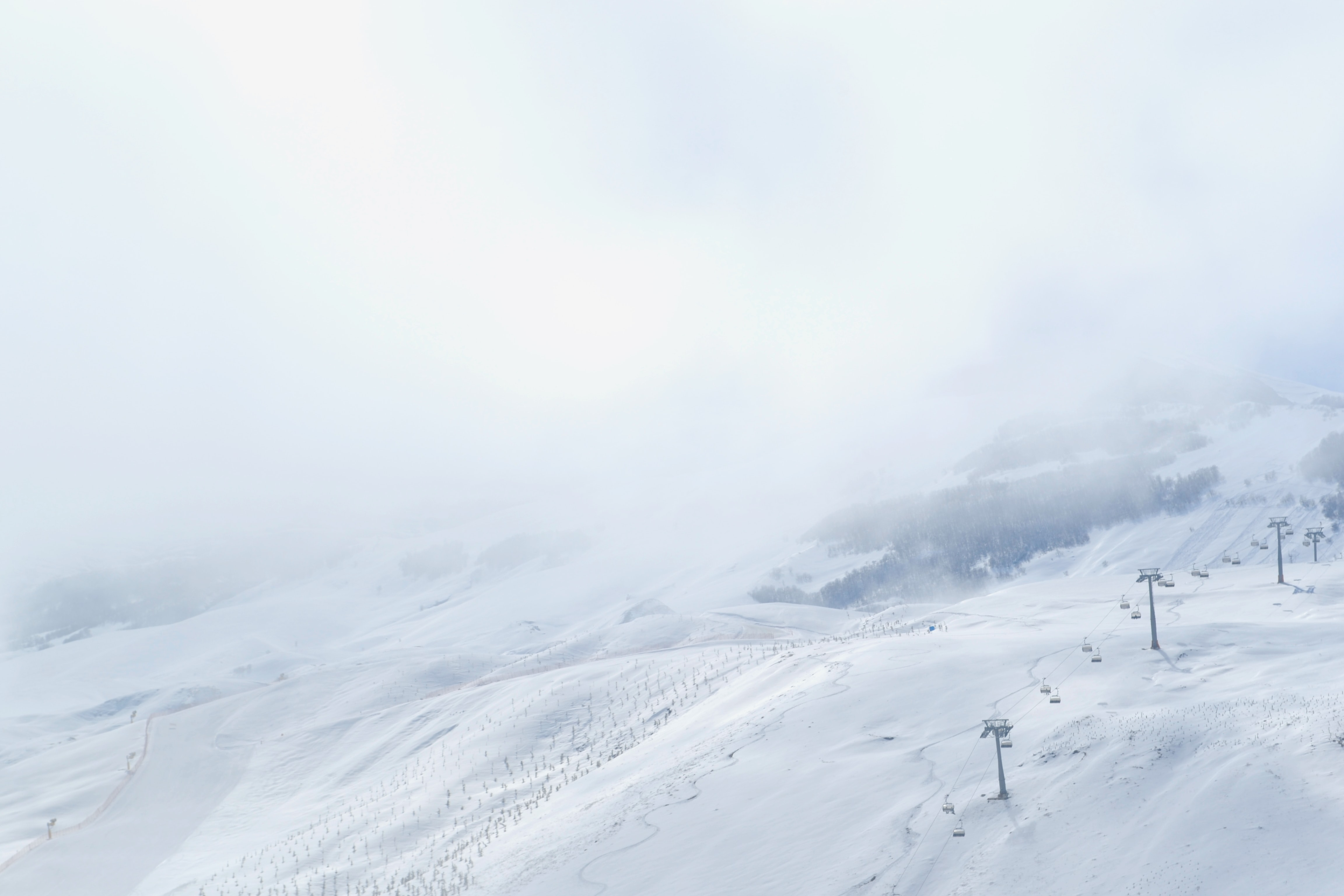 Snow covered and foggy mountain side with ski trails and a chairlift in Shahdag Mountain Resort