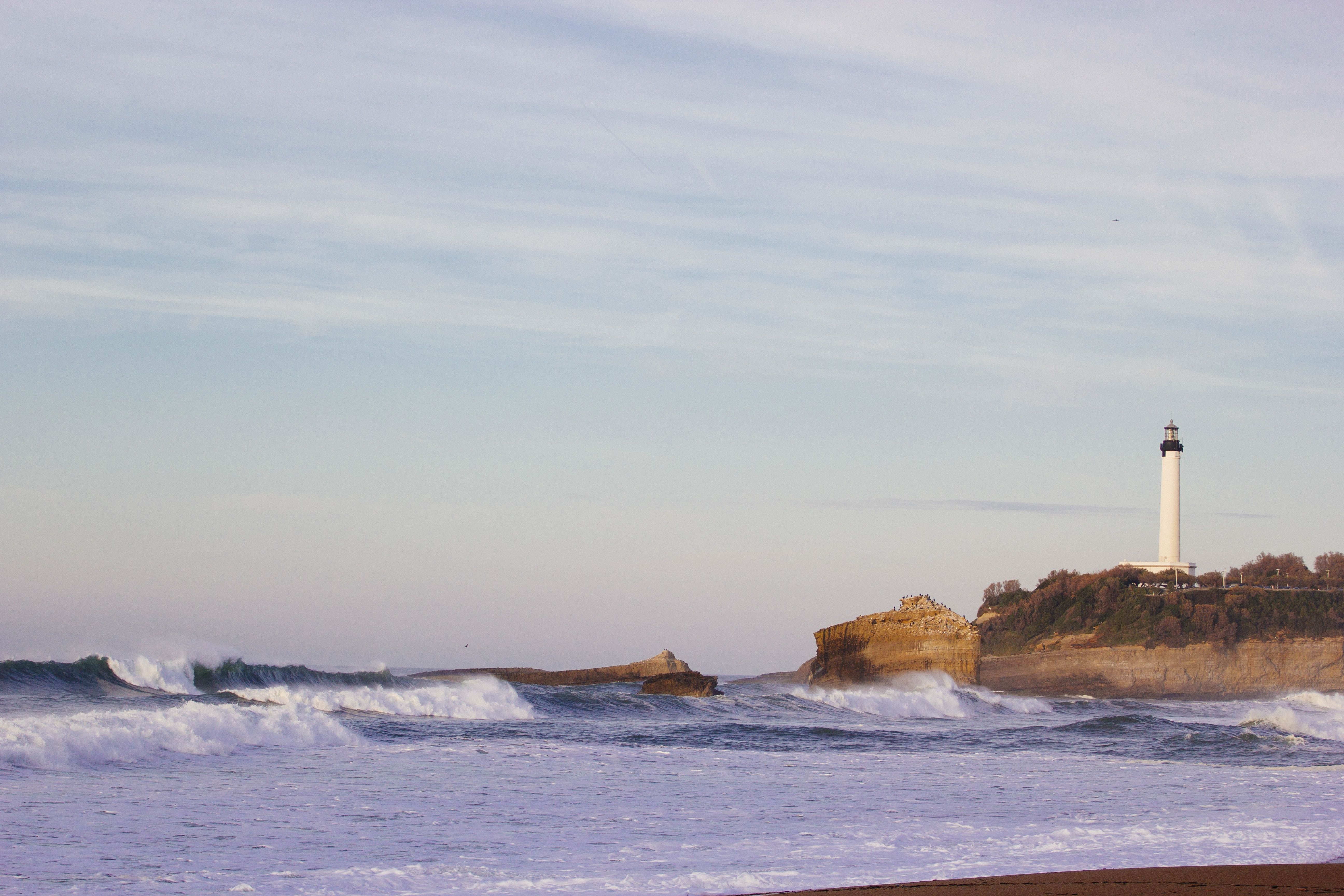 A coastal view of waves lapping the shoreline, with a white lighthouse in the distance at Biarritz