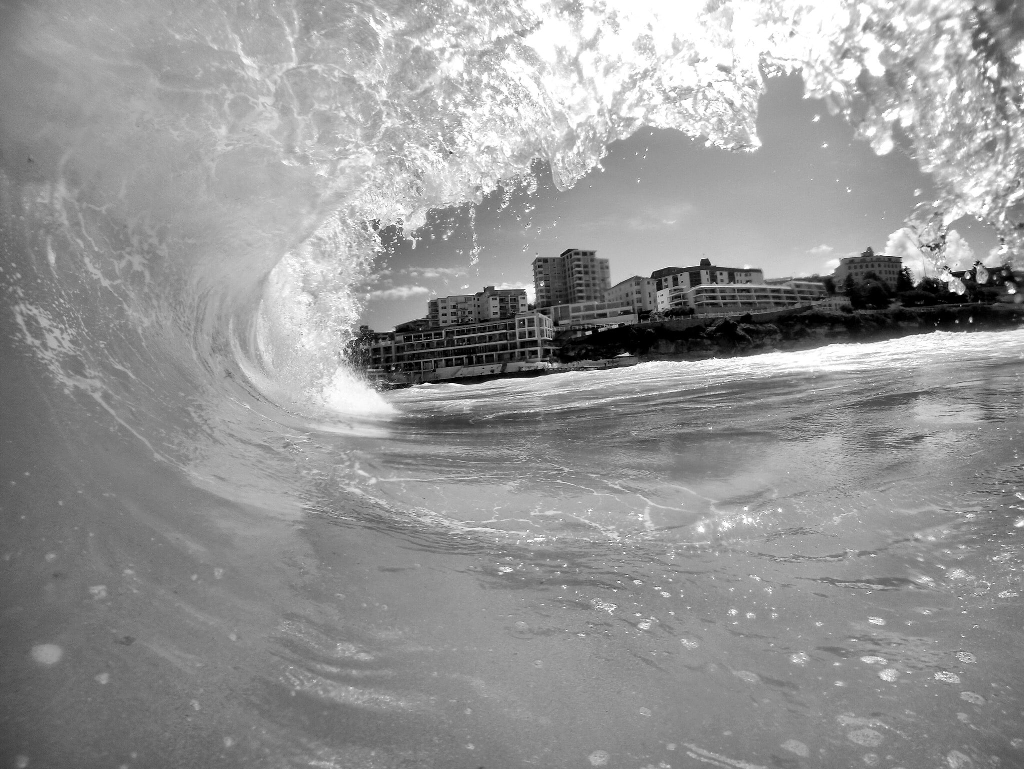 A gray image taken inside of a wave as it splashes overhead.