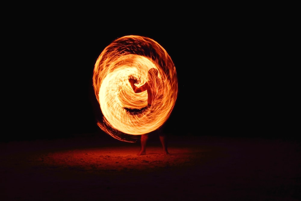 timelapse photography of person fire dancing