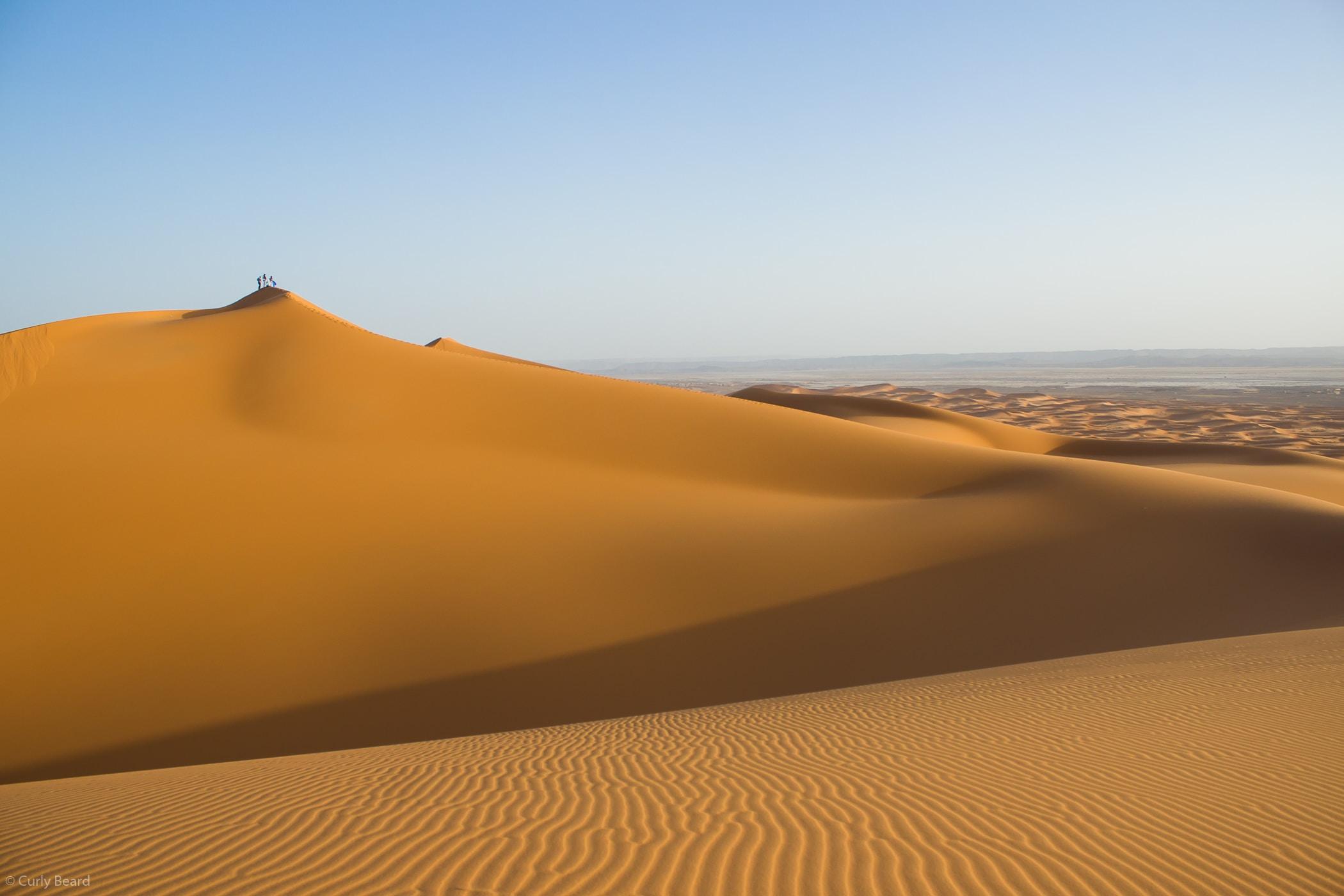 Hikers walk along sand ridges in the desert of Erg Chebbi