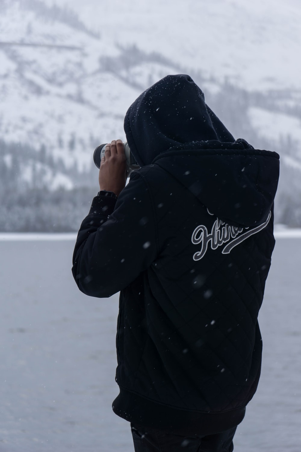 man wears hoodie takes picture during winter