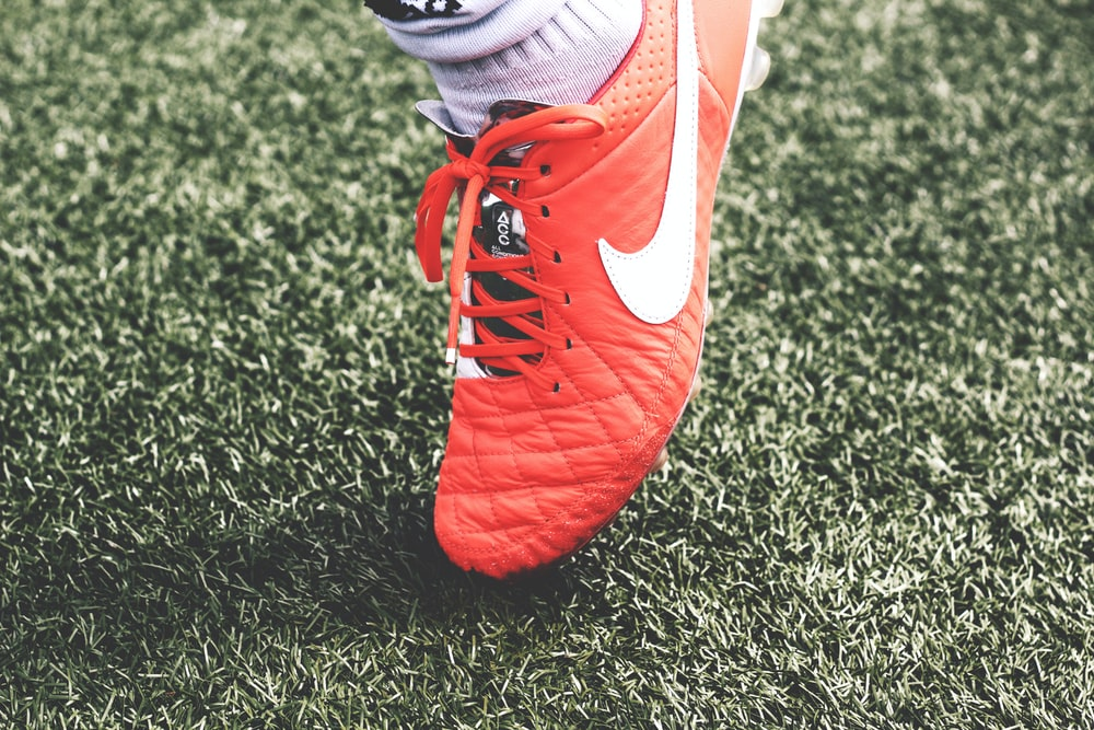 unpaired orange and white Nike soccer cleat