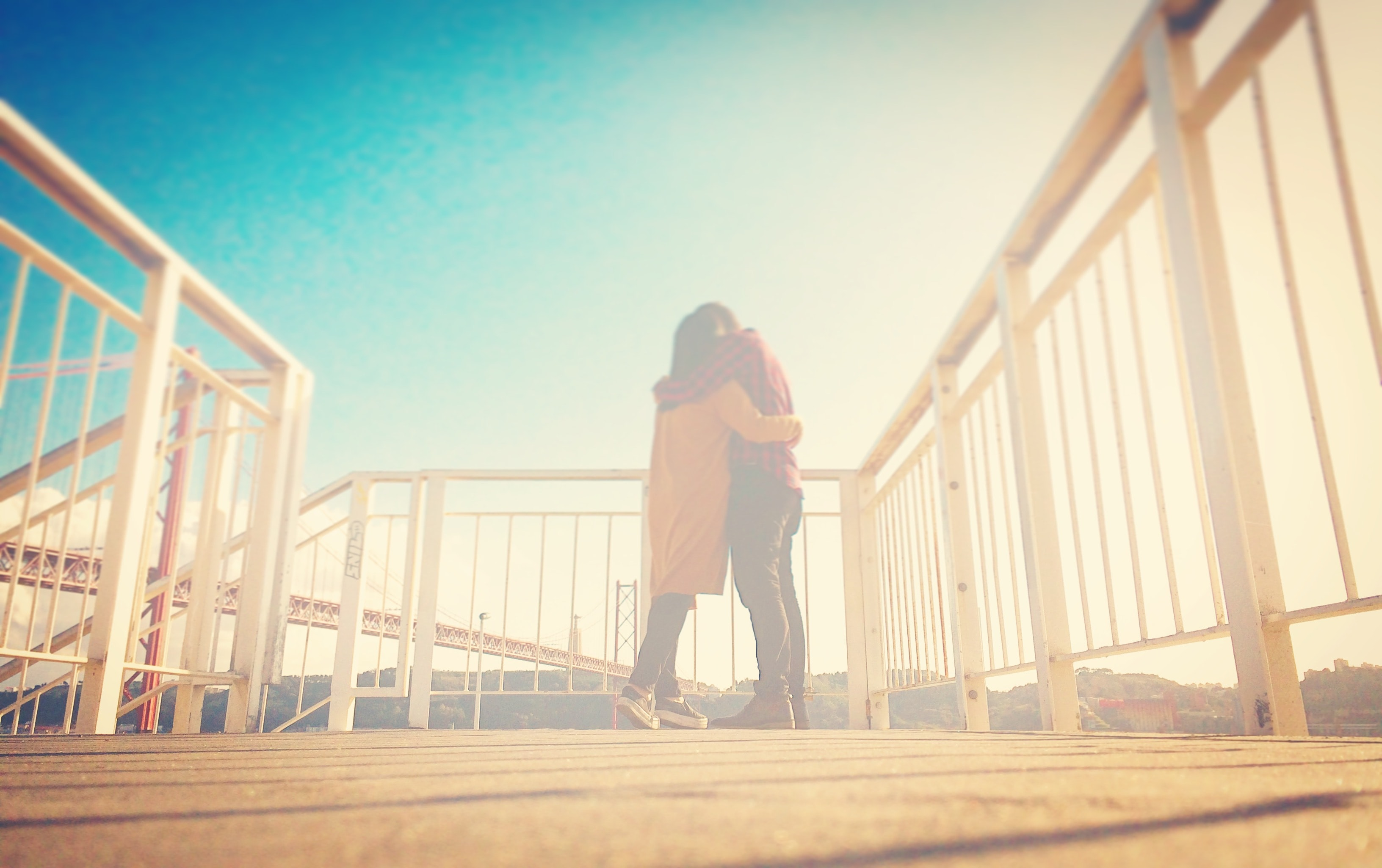 Soft light surrounds lovers on a boardwalk landing