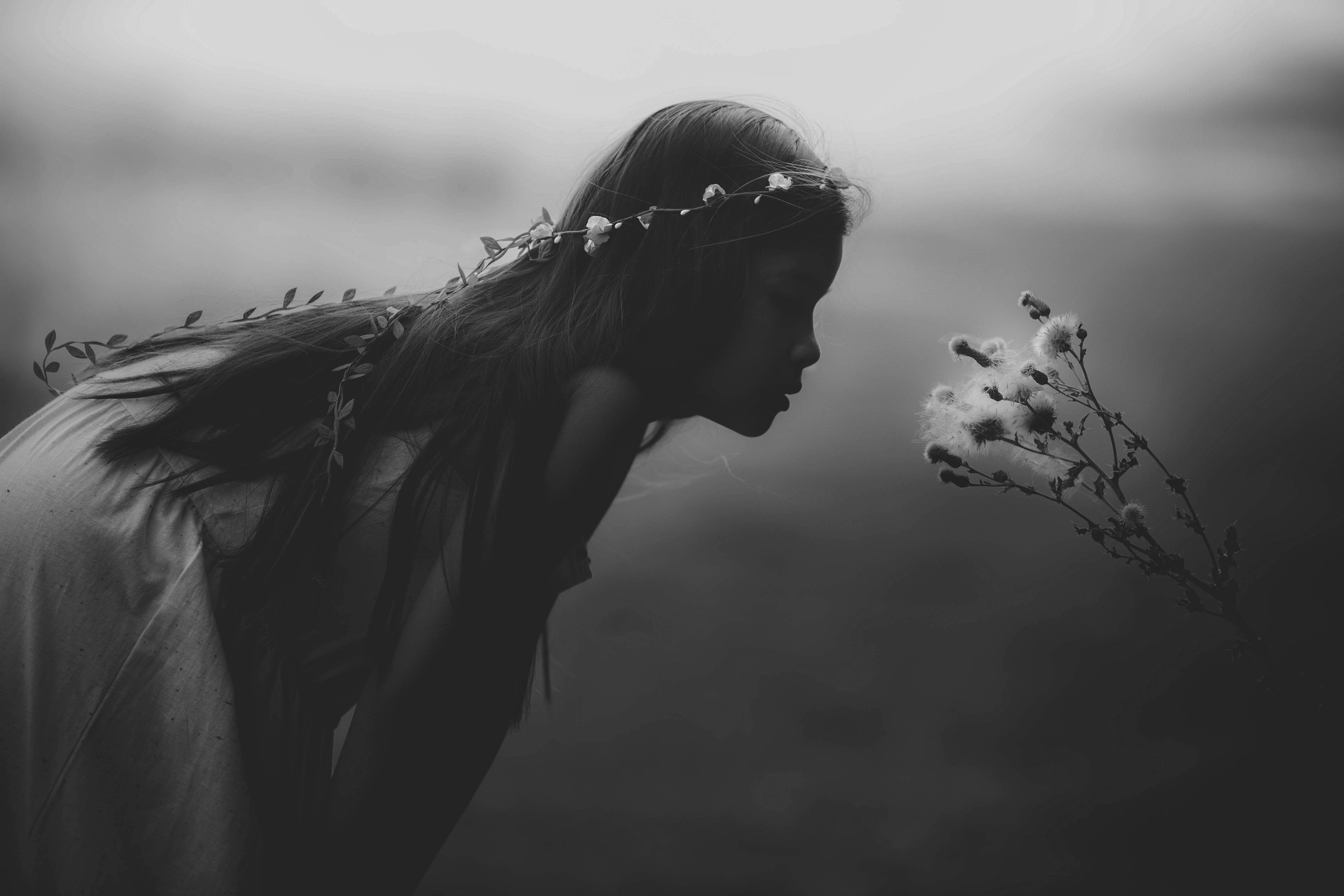 Black and white shot of young child with flower tiara blowing dandelion seedlings